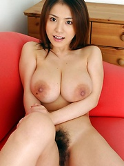 Anna Ohura posing huge natural tits in a red sofa