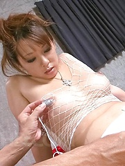 Asuka Asian has cans squeezed over fishnet and vibrator in peach